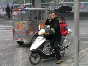 Elektroskůtry v Pekingu jsou běžné, ty se spalovacím motorem jsou raritou. S předpisy si ale hlavu nelámou, jízda bez helmy nebo na červenou jsou běžné. V pozadí je elektro-drožka.